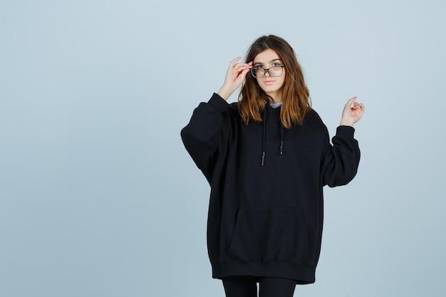 Jonge dame houdt de vingers op een bril terwijl ze terug wijst in een oversized hoodie, broek en er aantrekkelijk uitziet, vooraanzicht.
