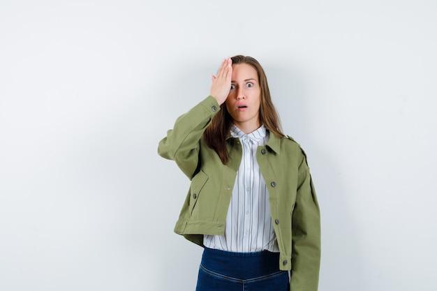 Jonge dame houdt hand in de buurt van oog in shirt, jas en kijkt geschokt, vooraanzicht.