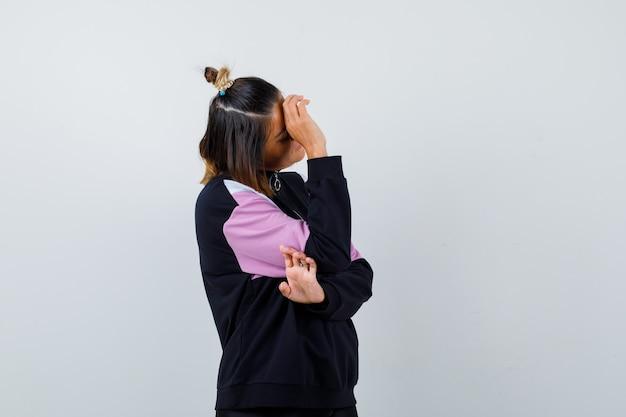 Jonge dame houdt hand op het voorhoofd in hoodie trui en ziet er moe uit.