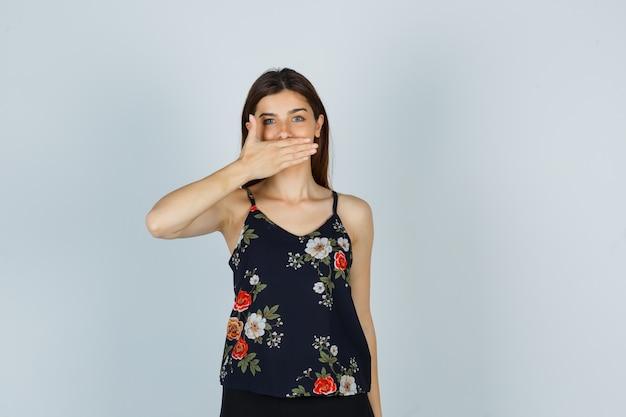 Jonge dame houdt hand op mond in blouse en ziet er positief uit, vooraanzicht.