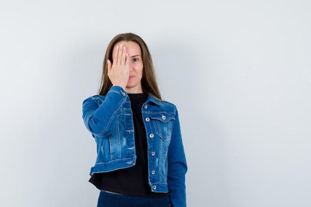 Jonge dame houdt hand op oog in blouse, jas en ziet er positief uit. vooraanzicht.