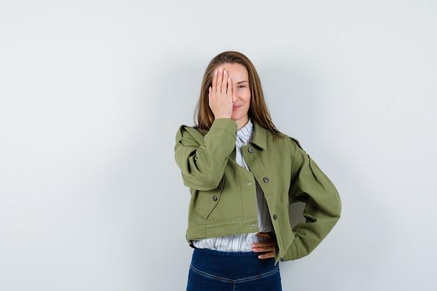 Jonge dame houdt hand op oog in overhemd, jasje en ziet er delicaat uit. vooraanzicht.