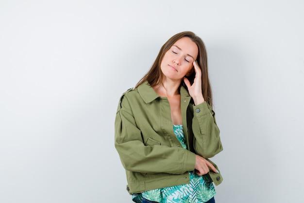 Jonge dame houdt hand op tempels in blouse, jas en ziet er slaperig uit, vooraanzicht.