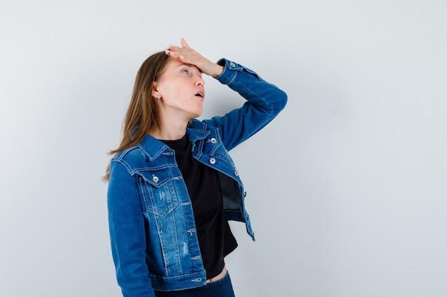 Jonge dame houdt hand op voorhoofd in blouse, jas en kijkt geïrriteerd. vooraanzicht.