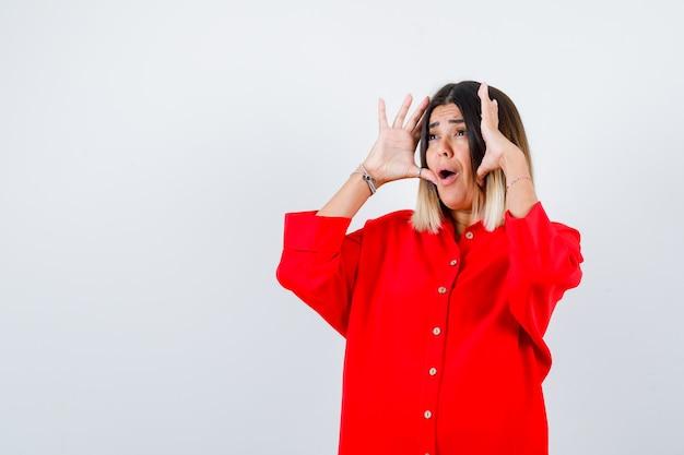 Jonge dame houdt handen in de buurt van het gezicht in een rood oversized shirt en kijkt bang vooraanzicht.