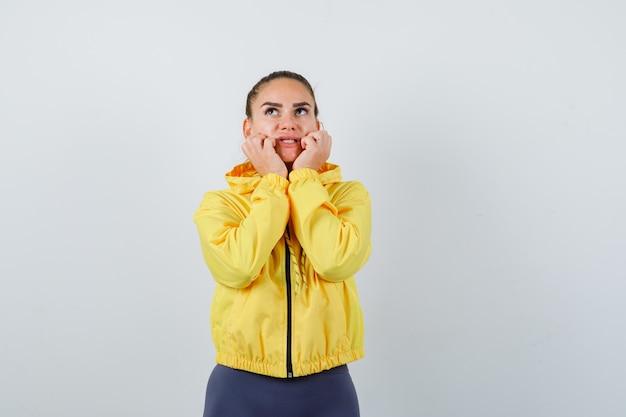 Jonge dame houdt handen in de buurt van mond in gele jas en ziet er bang uit, vooraanzicht.