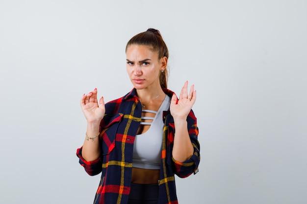 Jonge dame houdt handen in overgavegebaar in top, geruit hemd en ziet er serieus uit. vooraanzicht.