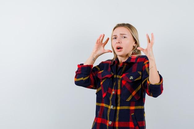 Jonge dame houdt handen op agressieve manier in geruit overhemd en kijkt woedend, vooraanzicht.