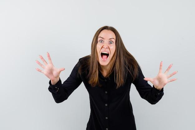 Jonge dame houdt handen op agressieve manier terwijl ze schreeuwt