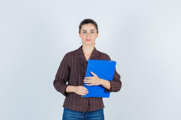 Jonge dame houdt map vast, kijkt naar camera in shirt, spijkerbroek en kijkt serieus, vooraanzicht.