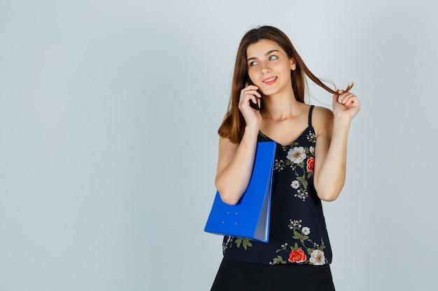Jonge dame houdt map vast, praat op mobiele telefoon, draait haar rond haar vingers in blouse, rok en ziet er vrolijk uit. vooraanzicht.