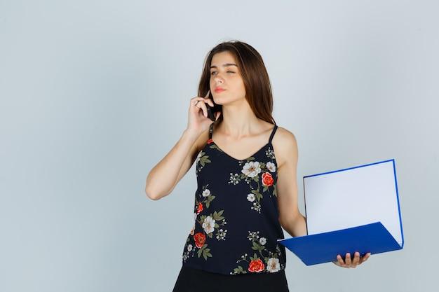 Jonge dame houdt map vast, praat op mobiele telefoon in blouse en ziet er attent uit. vooraanzicht.