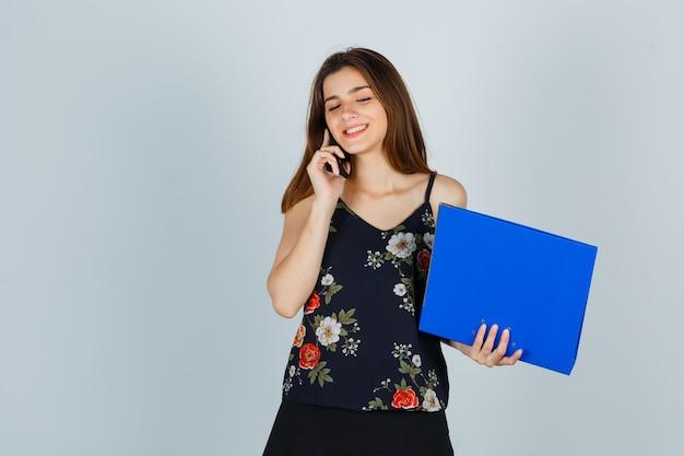 Jonge dame houdt map vast, praat op mobiele telefoon in blouse en ziet er vrolijk uit, vooraanzicht.