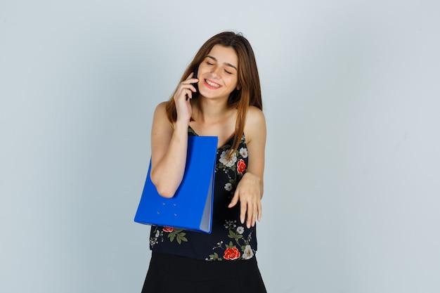 Jonge dame houdt map vast, praat op mobiele telefoon in blouse, rok en ziet er vrolijk uit. vooraanzicht.
