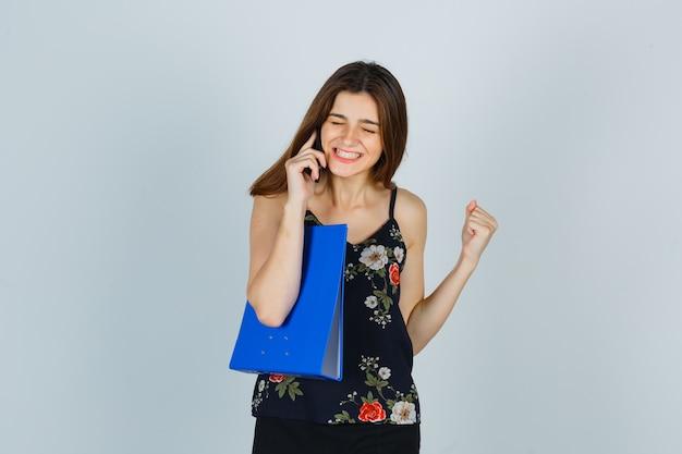 Jonge dame houdt map vast, praat op mobiele telefoon, toont winnaargebaar in blouse en ziet er zalig uit, vooraanzicht.