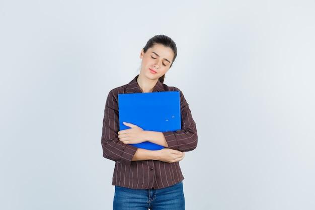 Jonge dame houdt map vast, sluit ogen in shirt, spijkerbroek en ziet er moe uit, vooraanzicht.