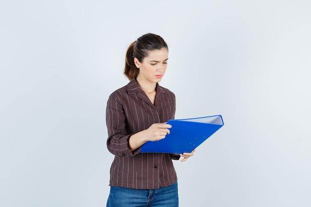 Jonge dame houdt map vast, staat zijwaarts in shirt, spijkerbroek en kijkt verbaasd.