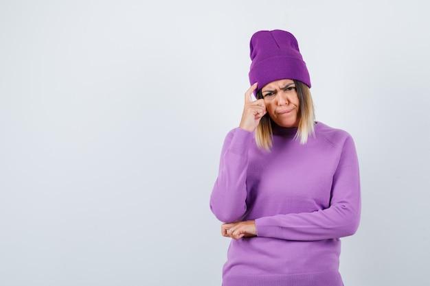 Jonge dame houdt vinger op het hoofd in paarse trui, muts en ziet er serieus uit, vooraanzicht.