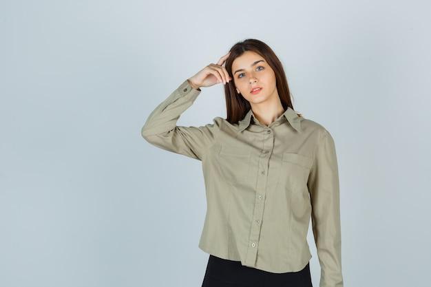 Jonge dame houdt vinger op hoofd in shirt, rok en kijkt attent, vooraanzicht.