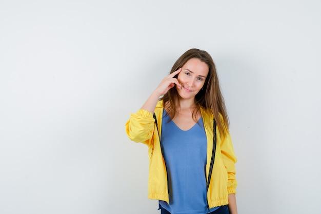 Jonge dame houdt vinger op tempels in t-shirt, jas en ziet er intelligent uit, vooraanzicht.