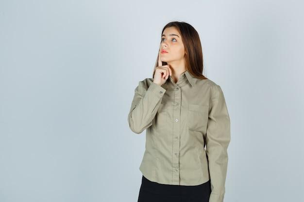 Jonge dame houdt vinger op wang in shirt, rok en kijkt attent, vooraanzicht.