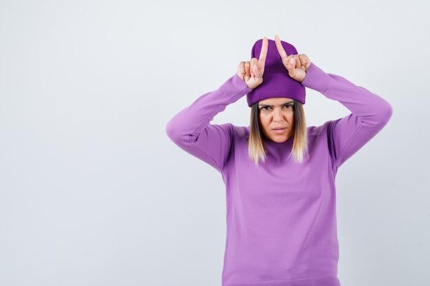 Jonge dame houdt vingers boven het hoofd als stierenhoorns in paarse trui, muts en kijkt geamuseerd, vooraanzicht.