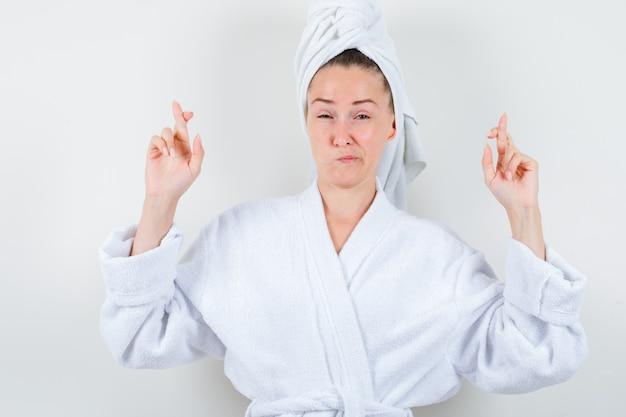 Jonge dame houdt vingers gekruist in witte badjas, handdoek en kijkt ontevreden, vooraanzicht.
