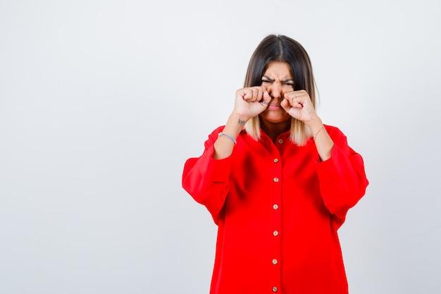 Jonge dame huilt terwijl ze in de ogen wrijft met de handen in een rood oversized shirt en er bedroefd uitziet, vooraanzicht.