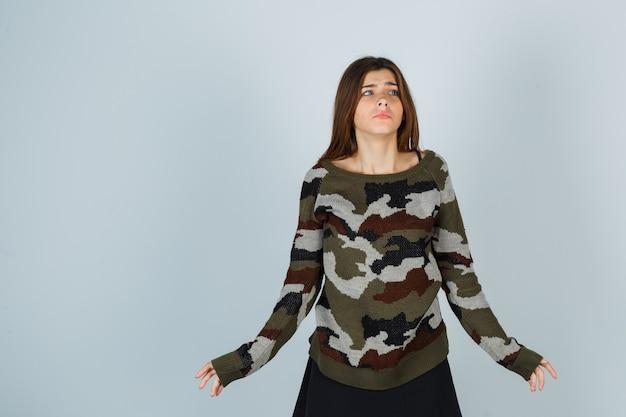 Jonge dame hulpeloos gebaar in trui tonen en angstig kijken