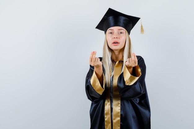Jonge dame in academische jurk die geldgebaar toont en er zelfverzekerd uitziet