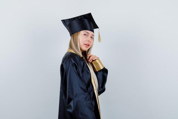 Jonge dame in academische jurk poseren terwijl ze staat en ziet er prachtig uit