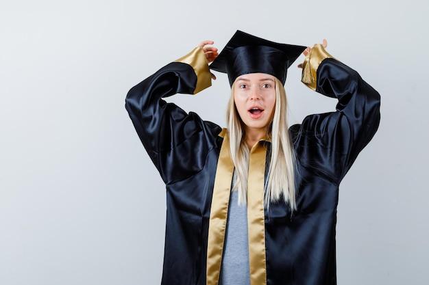 Jonge dame in academische kleding die handen op een agressieve manier houdt en er vergeetachtig uitziet