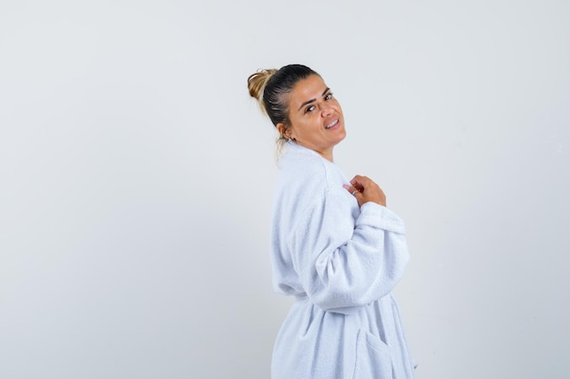 Jonge dame in badjas die over haar schouder kijkt en er positief uitziet
