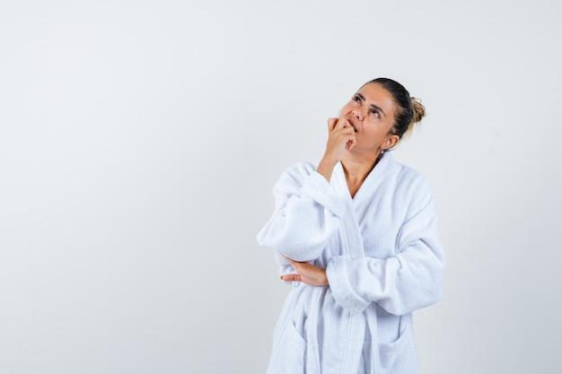 Jonge dame in badjas staat in denkende pose en ziet er attent uit