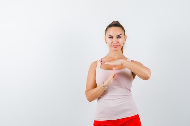 Jonge dame in beige mouwloos onderhemd dat het gebaar van de tijdpauze toont en er zelfverzekerd uitziet