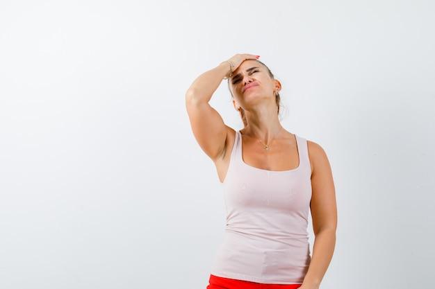 Jonge dame in beige tanktop die hand op hoofd houdt en moe, vooraanzicht kijkt.