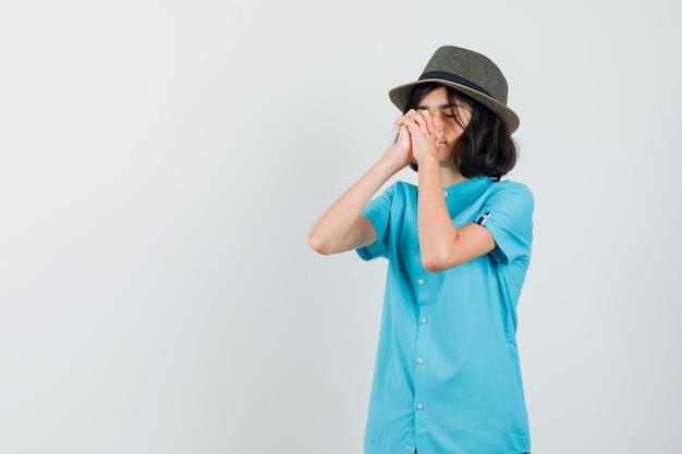 Jonge dame in blauw overhemd, hoed die handen combineert om te bidden en hoopvol te kijken