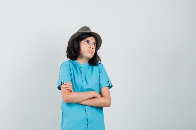 Jonge dame in blauw overhemd, hoed die zich met gekruiste wapens bevindt terwijl opzij kijkt en gecompliceerd kijkt
