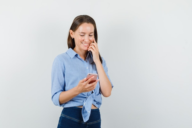 Jonge dame in blauw shirt, broek die mobiele telefoon onderzoekt en vrolijk kijkt