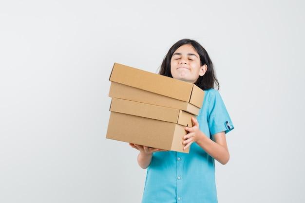 Jonge dame in blauw shirt met zware dozen en ziet er ingewikkeld uit