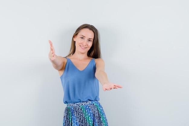Jonge dame in blauwe blouse, rok die armen opheft om iemand te knuffelen en oprecht, vooraanzicht te kijken.