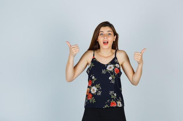 Jonge dame in bloemenbovenkant duimen opdagen en geschokt kijken
