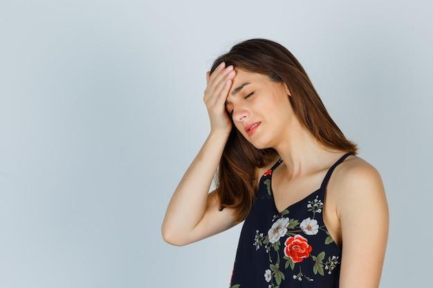 Jonge dame in bloementop die aan hoofdpijn lijdt, zijwaarts staat en boos kijkt.