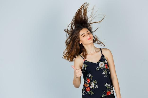 Jonge dame in bloementop die duim toont en zelfverzekerd kijkt