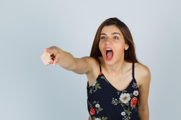 Jonge dame in bloementop die naar iemand richt terwijl ze schreeuwt en boos kijkt