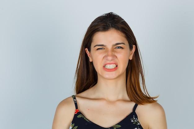 Jonge dame in bloementop die tanden toont en boos kijkt