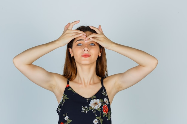 Jonge dame in blouse die haar puistje op het voorhoofd knijpt en er zelfverzekerd uitziet, vooraanzicht.