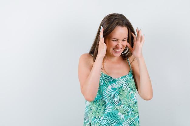 Jonge dame in blouse die handen in de buurt van het hoofd opheft en er geïrriteerd uitziet, vooraanzicht.