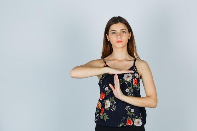 Jonge dame in blouse die het gebaar van de tijdonderbreking toont en er serieus uitziet, vooraanzicht.