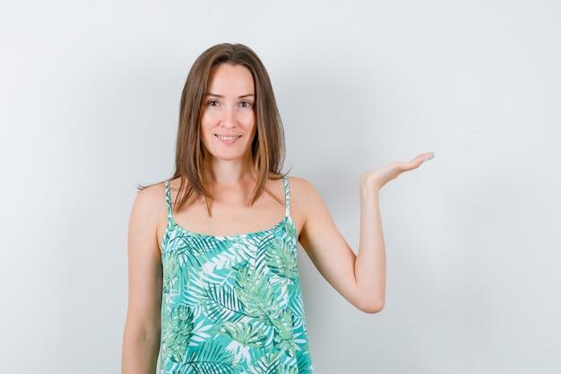 Jonge dame in blouse die iets vasthoudt en er vrolijk uitziet, vooraanzicht.